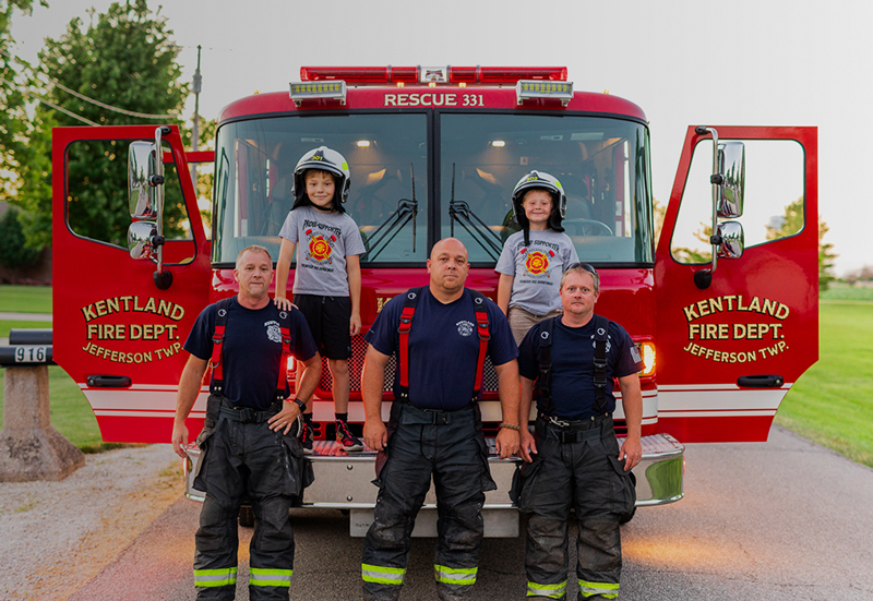 Fire Department, Three firefighters and two boys standing in front of fire truck 800x551