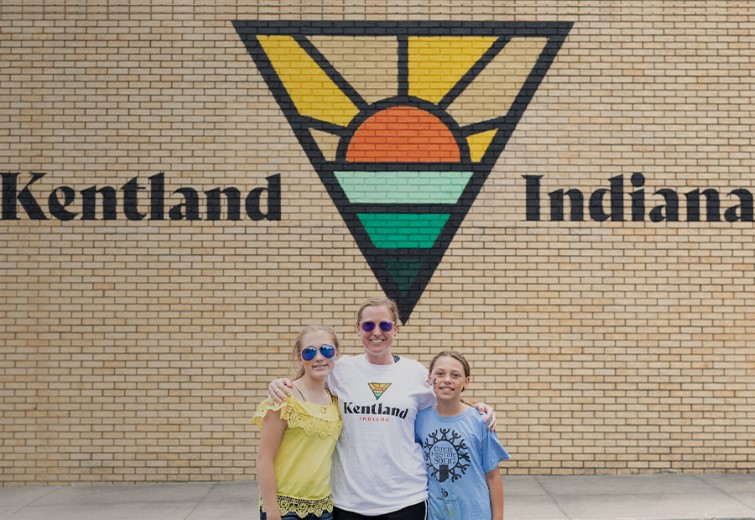 Mom and two daughters posing in front of the Kentland Indiana Mural